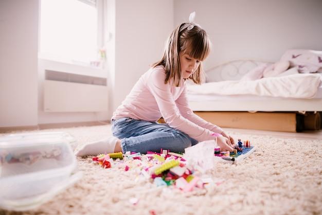 Menina pequena criança pensativa bonita sentada no tapete de seu quarto brilhante e brincando com brinquedos de plástico.