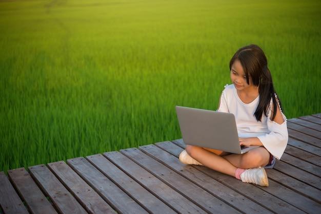 Menina pequena da ásia que usa o conceito do ensino electrónico do portátil de digitas