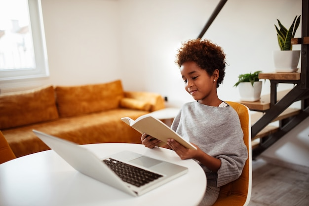 Menina pequena de sorriso da misturado-raça que lê um livro.