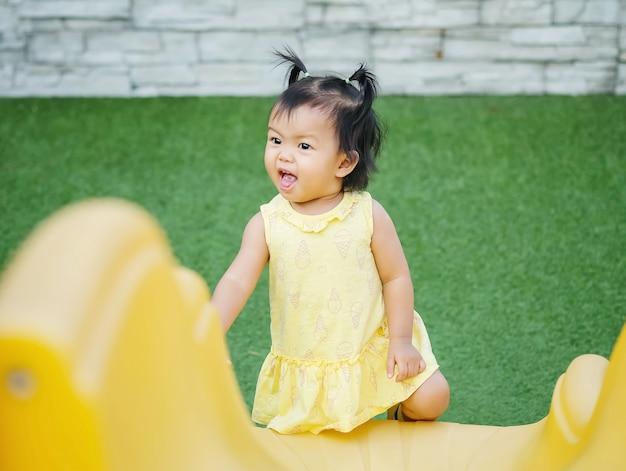 Menina pequena do close up com movimento engraçado quando joga um slider no fundo do campo de jogos