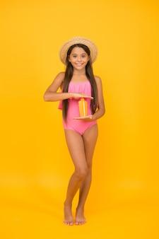 Menina pequena em traje de banho segurar creme de cosméticos de protetor solar, pele calmante após o conceito de bronzeamento.