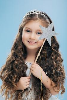 Menina pequena fada com cabelos escuros encaracolados, usa coroa e vestido, tem olhos azuis, sorriso gentil