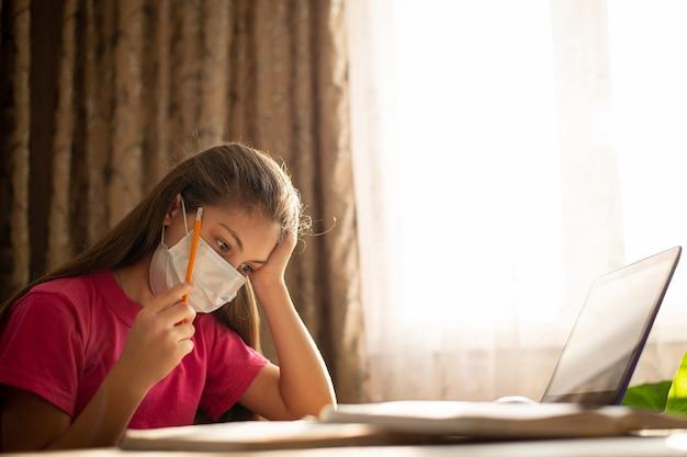 Menina pequena na máscara médica estudando em casa. estudante diligente pensando, fazendo exercícios, preparando a lição de casa