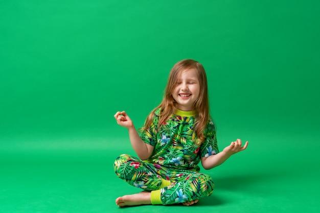 Menina pequena no vestido estampado floral, sentado na posição de lótus, com as pernas cruzadas