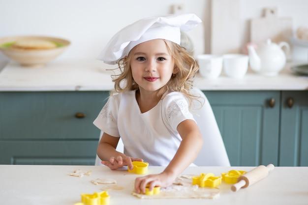 Menina pequena padeiro ou cozinheiro corta massa para biscoitos na cozinha com forma