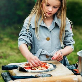 Menina pequena que cozinha o conceito da pizza