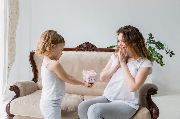 Menina pequena que dá o presente do dia de mãe a sua mãe surpreendida