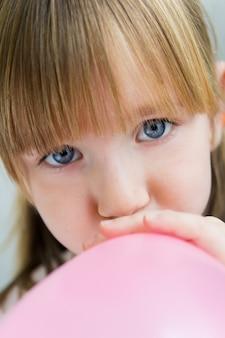 Menina pequena que infla um balão rosa na cozinha
