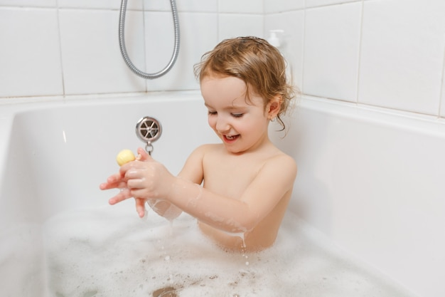 Menina pequena tomando banho com espuma em uma banheira brincando com um brinquedo.
