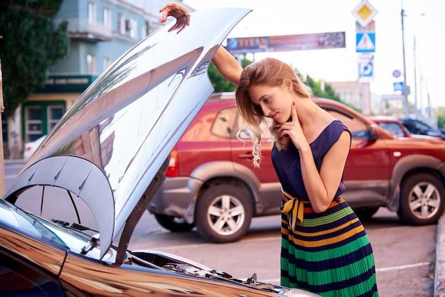 Menina perplexa perto do carro com um capô aberto.