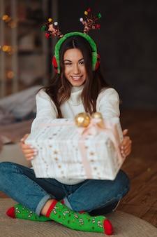 Menina perto com presente sorrindo para a câmera. ela está usando chifres de natal.