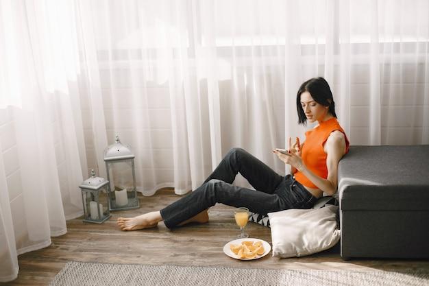 Menina perto da janela no chão usando um telefone celular.