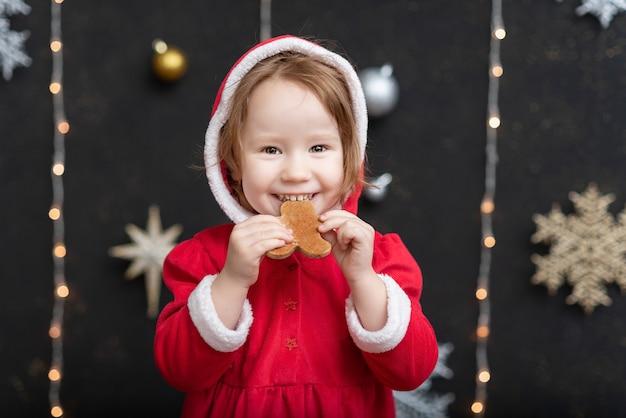 Menina perto de árvore de natal faz um desejo de ano novo com os olhos fechados.