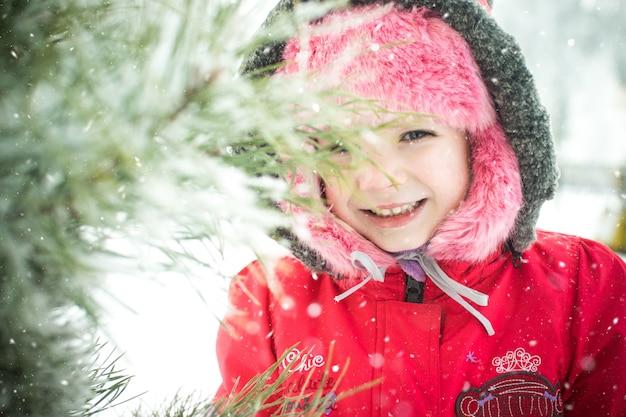 Menina perto de um galho de pinheiro no parque