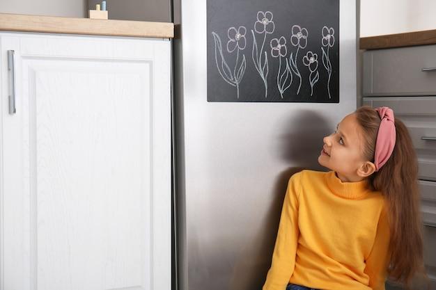 Menina perto do quadro-negro na geladeira na cozinha