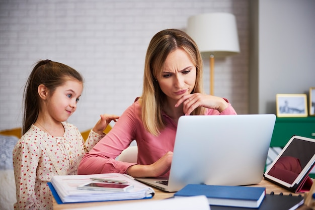 Menina perturbando a mãe para trabalhar em casa