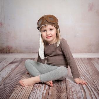 Menina-piloto bonitinho no chapéu