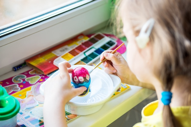 Menina pinta um ovo de páscoa com cores brilhantes