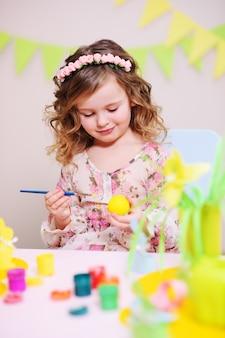 Menina pinta um ovo na superfície da decoração de páscoa.