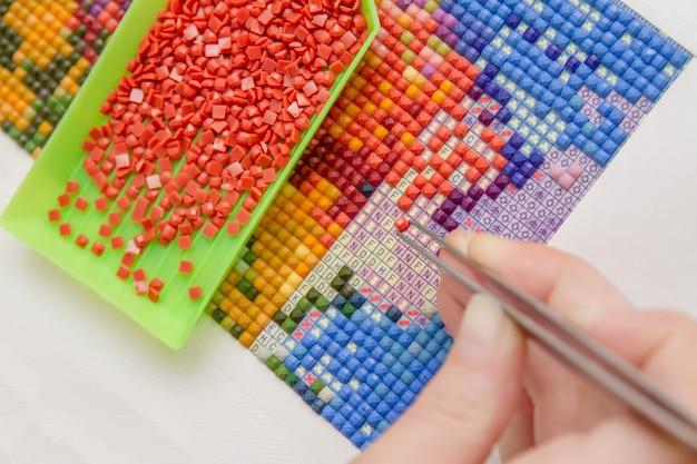 Menina pintando com diamantes coloridos e usando uma pinça