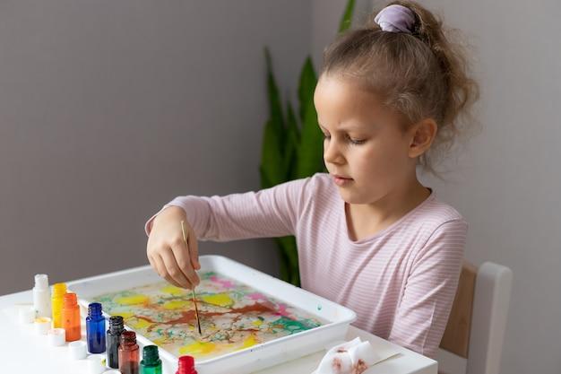 Menina pintando com tintas na água. arte ebru