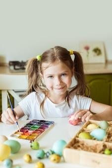Menina pintando ovos de páscoa artesanais com tinta acrílica