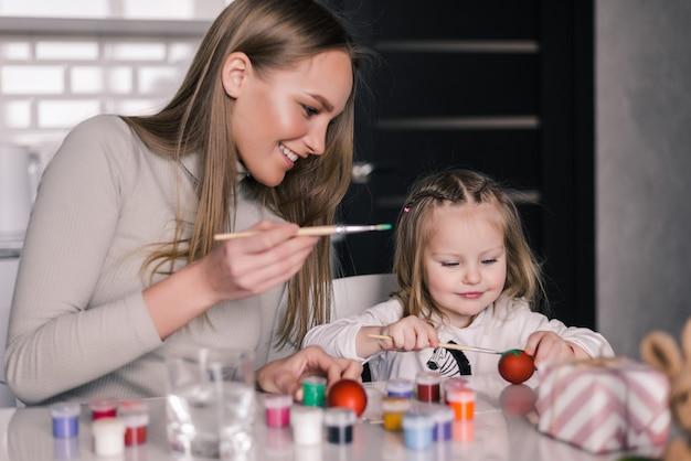 Menina pintando ovos de páscoa com a mãe na cozinha