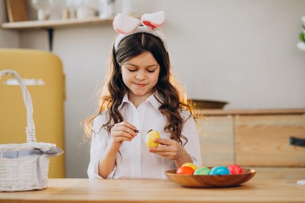 Menina pintando ovos para a páscoa