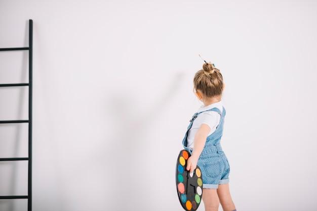 Menina pintando parede de luz com pincel