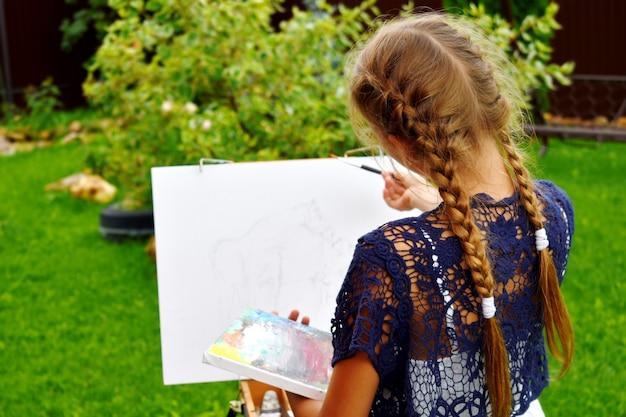 Menina pintando uma imagem em um caderno de desenho ao ar livre