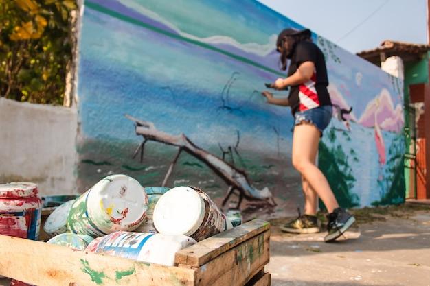 Menina pintando uma parede de rua com pincéis.