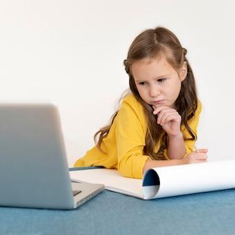 Menina pintando usando paleta e laptop