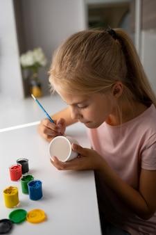 Menina pintando vaso em casa