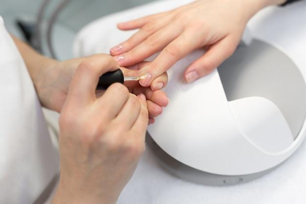 Menina pintar as unhas no salão de manicure, close-up. master aplica verniz em unhas em salão de manicure. mulher recebendo unhas manicure no salão. cuidar das mãos