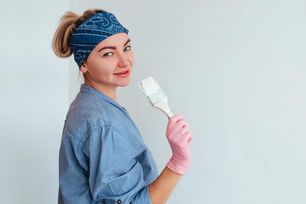 Menina pintora com camisa azul sorrindo pintando a parede
