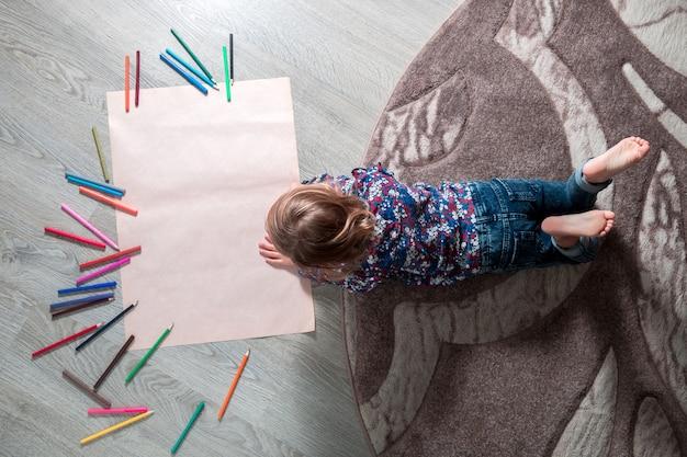 Menina pintura, desenho. criança deitada no chão perto de giz de cera.