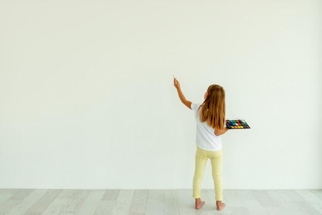 Menina pintura na parede branca dentro de casa