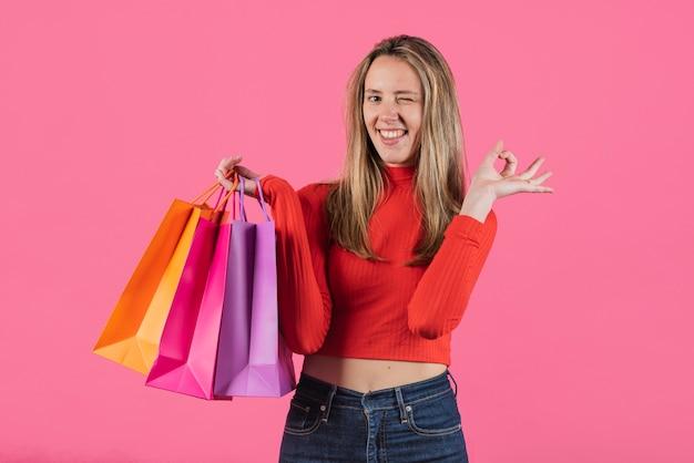 Menina piscando segurando sacolas de compras