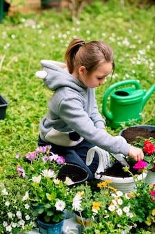 Menina plantando flores com cuidado em uma panela para varanda no quintal.