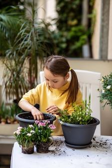 Menina plantando flores com entusiasmo em um vaso na varanda