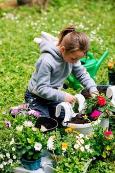 Menina plantando flores em uma panela para varanda no quintal.
