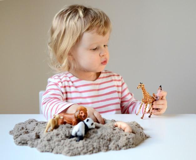 Menina plyaying com areia cinética e animais de brinquedo