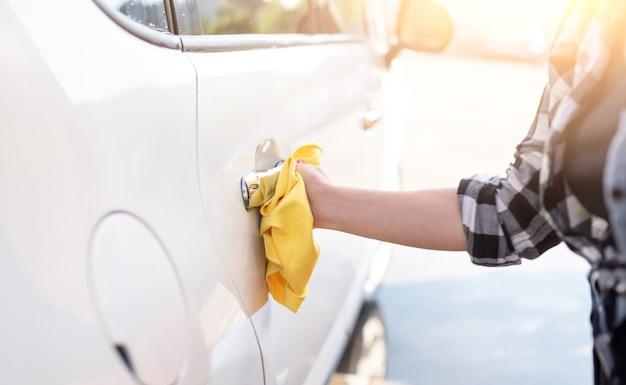 Menina polindo a maçaneta da porta do carro com um pano de microfibra close-up