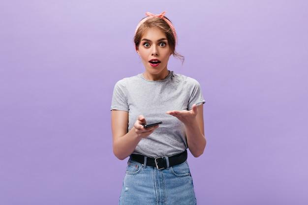 Menina posa com mal-entendido e segura o telefone. mulher legal em bandana rosa com batom vermelho, olhando para a câmera no fundo isolado.