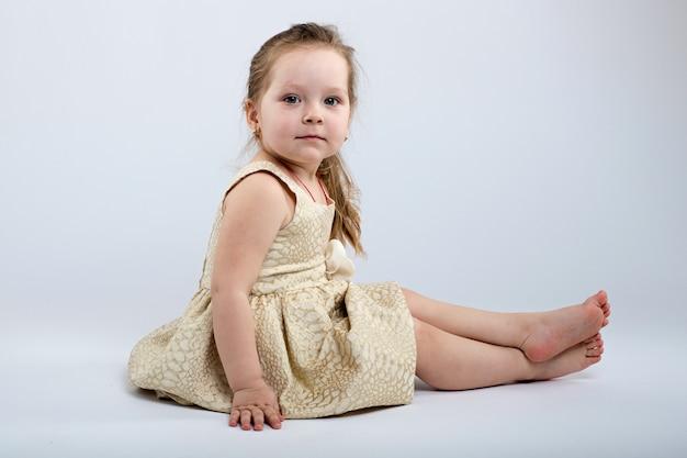 Menina posa em lindo vestido em fundo cinza
