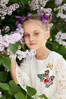 Menina posa em um arbusto de lilases na primavera. retrato romântico de uma criança em flores sob a luz do sol