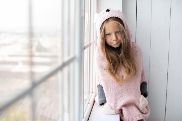 Menina posando ao lado de uma janela