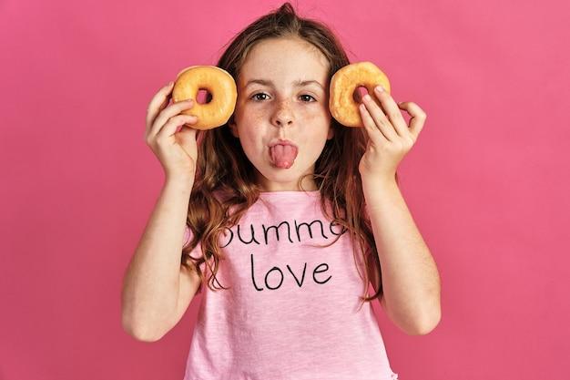 Menina posando com alguns donuts em uma parede rosa