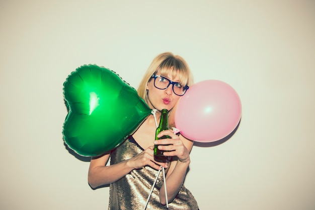 Menina posando com balões e cerveja