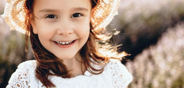 Menina posando com um chapéu em um campo de lavanda, enquanto olha para a câmera